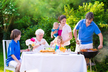 Big happy family enjoying bbq grill in the garden