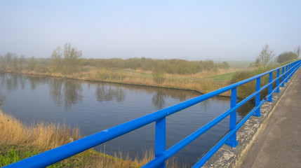 Blue bridge railing over a foggy canal in spring
