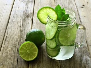 Detox water with lime and cucumbers in jar against rustic wood