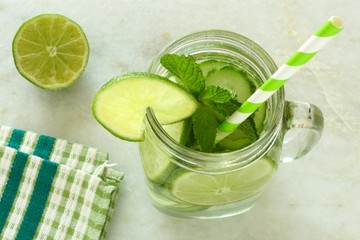 Detox water with lime and cucumbers in a jar on white marble