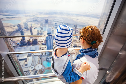 Young woman and son looking out of window from Burj Khalifa
