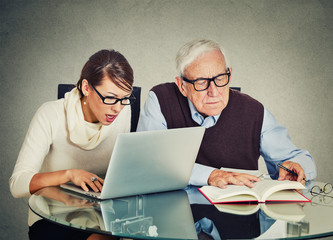 woman working on laptop and older grandpa man reading from book