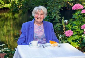 Happy Senior Woman Having Snacks at the Garden.