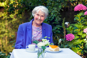 Smiling Old Woman with Snacks at the Garden Table.