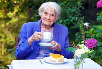 Elderly Woman Drinking Coffee at the Garden Table.