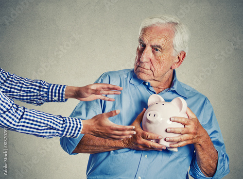 senior man holding piggy bank suspicious protecting savings - 81370781