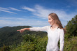 girl stands on a hilltop points into the distance