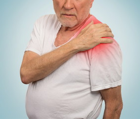 senior man with pain in his shoulder isolated blue background .