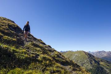 Ragazza cammina su una cresta in montagna