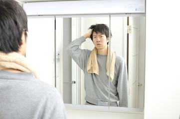 朝起きて自宅の洗面台の鏡に映る眠そうな自分を見つめる日本人男性
