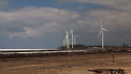Wind Turbines Over A Frozen Lake. Time-Lapse.