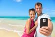 Beach vacation couple taking selfie on smartphone