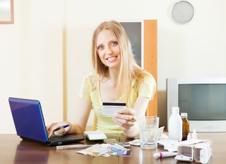 happy woman   paying medications by  card in internet store