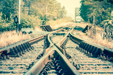 Close up railway track crossing before metal bridge