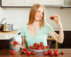 Positive woman eating strawberry in home