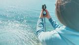 Traveler woman holding a compass on coast