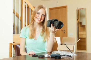 woman unpacking new digital camera at home