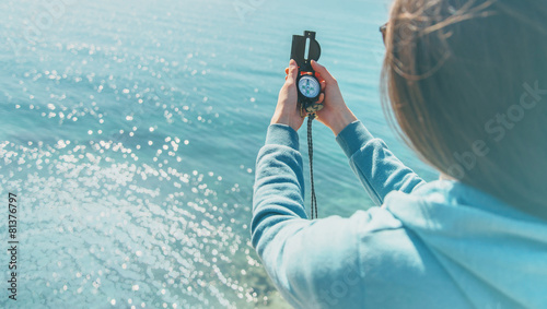 Traveler woman holding a compass on coast - 81376797
