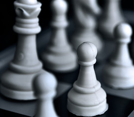 Pawn of white figures on a chessboard against a dark background.