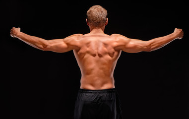 Rear view of sexy muscular sportsman with arms stretched out