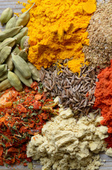 Assorted spices and dry herbs on wooden background