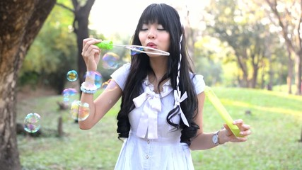 Asian Thai girl is blowing a soap bubbles in the park