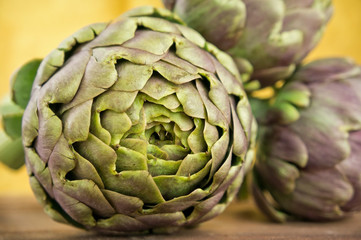 Group of fresh artichokes on wooden table