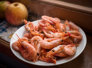 Cooked shrimps on white plate. Shallow depth of field.