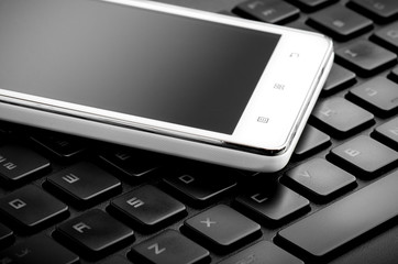 White Smart Phone On Keyboard Close Up