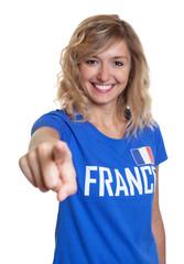 Weiblicher Frankreich-Fan mit blonden Locken zeigt zur Kamera