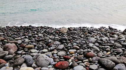 Stones with waves on beach of shore or coast of ocean or sea