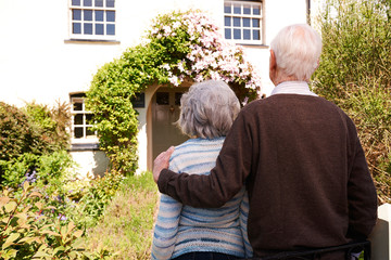 Rear View Of Senior Couple Outside Pretty Cottage
