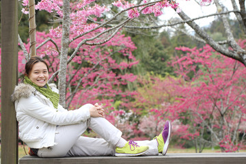 Chinese woman sit and enjoy in Cherry blossom garden
