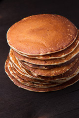 Stack of delicious pancakes on black