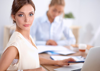 Two women working together at office, sitting on the desk