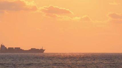 ship on horizon of sea at sunset