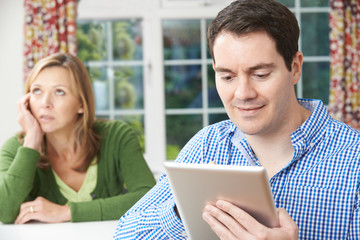Unhappy Woman Sitting At Table As Partner Uses Digital Tablet