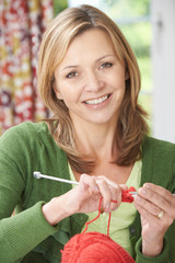 Portrait Of Woman Enjoying Knitting Garment At Home