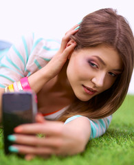 beautiful young woman making selfie by her phone while lying in