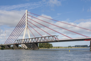 Deconstruction of an old bridge next to a new suspension bridge