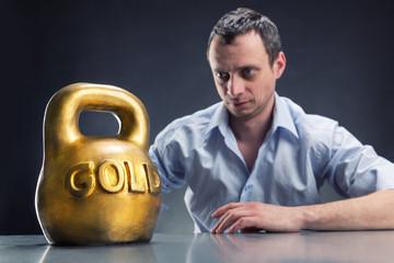 Businessman looks at a gold kettlebell
