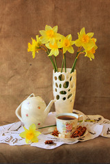 Cup of tea and a vase with daffodils..