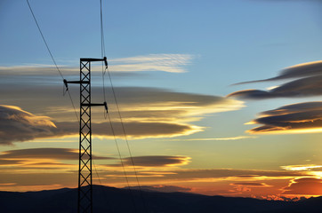 Electric pole power lines and wires at sunset