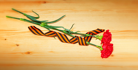 Two carnation flowers and George Ribbon. May 9 Victory Day