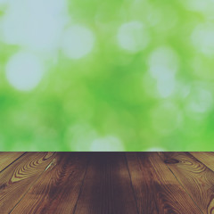 Wood table and bokeh abstract nature green background with vinta