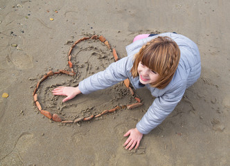 Bambina sulla spiaggia disegna un cuore
