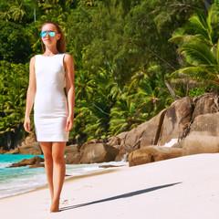Woman wearing dress on beach at Seychelles