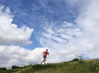 Male runner on grassy embankment