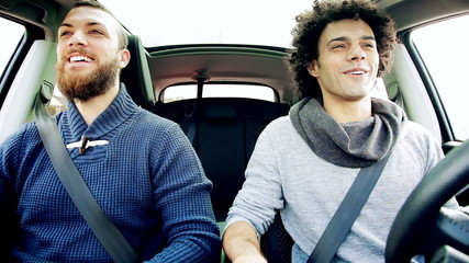 Two happy men laughing in car strong friendship