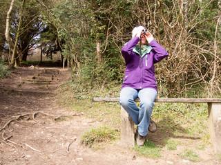 Woman looking through a pair of Binoculars